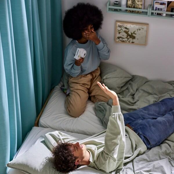 Mężczyzna i kobieta na dwóch łóżkach z zieloną pościelą BERGPALM w paski i jasną pościelą SPJUTVIAL w różnych odcieniach szarości. Obok wisi zasłona.