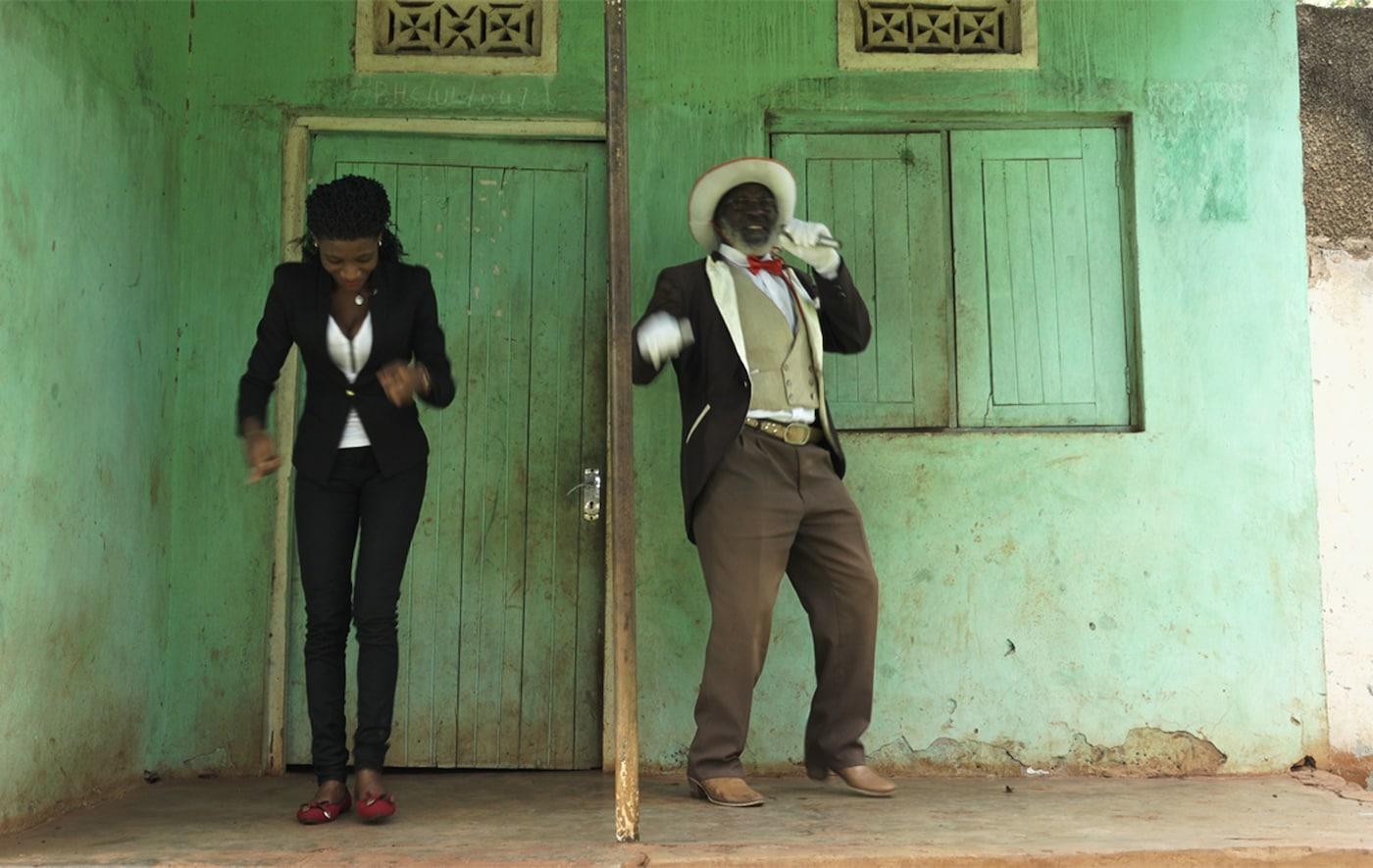 Mężczyzna i kobieta w eleganckich ubraniach tańczą przed zielonym budynkiem.