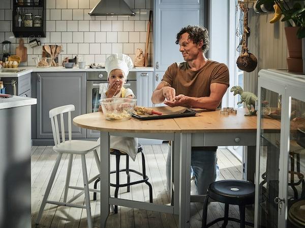 Mężczyzna robiący ciastka z dzieckiem przy stole kuchnnym.