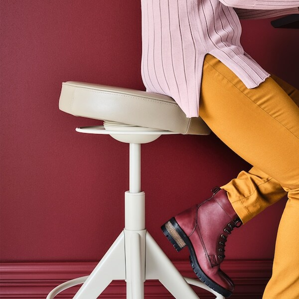 mezczyzna siedzacy na biurowym obrotowym stolku, wykonanym z jasnej skory. Mezczyzna ubrany w zolte spodnie, bordowe buty na tle bordowej sciany.