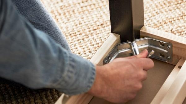 Mężczyzna skręcający stół na dywanie.