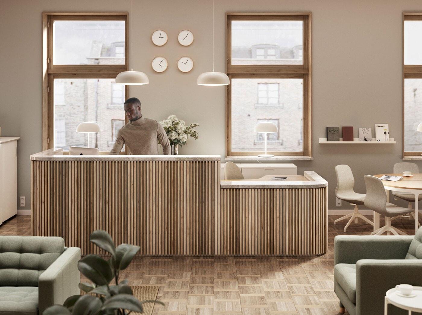 Mężczyzna stojący za umiejscowioną pod dwoma oknami ladą recepcji z jasnego drewna. Nad recepcję wiszą dwie lampy wiszące NYMÅNE, a na ścianie znajdują się cztery zegary.