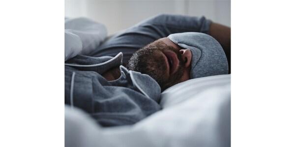 Mężczyzna w niebieskiej piżamie i dopasowanej masce na oczy śpi w łóżku z otwartymi ustami.