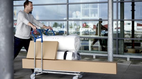 Meżczyzna wiązący zakupy na wózku platformowym na tle sklepu.