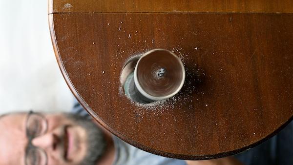 Mężczyzna wykonuje za pomocą wiertarki elektrycznej otwór w ciemnobrązowym blacie okrągłego drewnianego stolika.