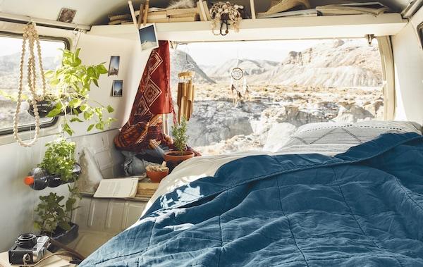 مفرش سرير أزرق في مركبة في اتجاه الجبال.