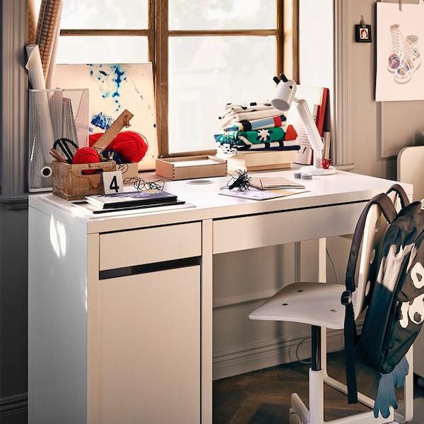 MICKE kinderbureau waarop boeken en andere school artikelen op liggen | IKEA