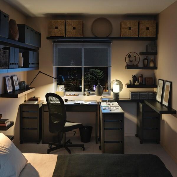 MICKE Schreibtisch in schwarz mit Schubladenelementen und einem Drehstuhl.