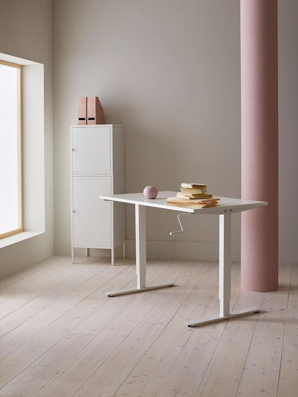 midden in een kale ruimte staat een witte bureau met enkele boeken en een witten kast met twee lektuurbakken bovenop