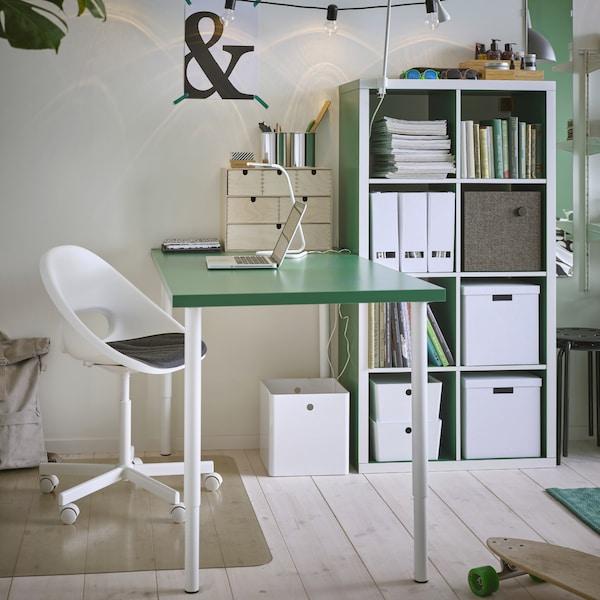 Miejsce do nauki z zielonym stołem na białych nogach, białym krzesłem obrotowym, białą lampą biurkową i przezroczystym ochraniaczem podłogi.