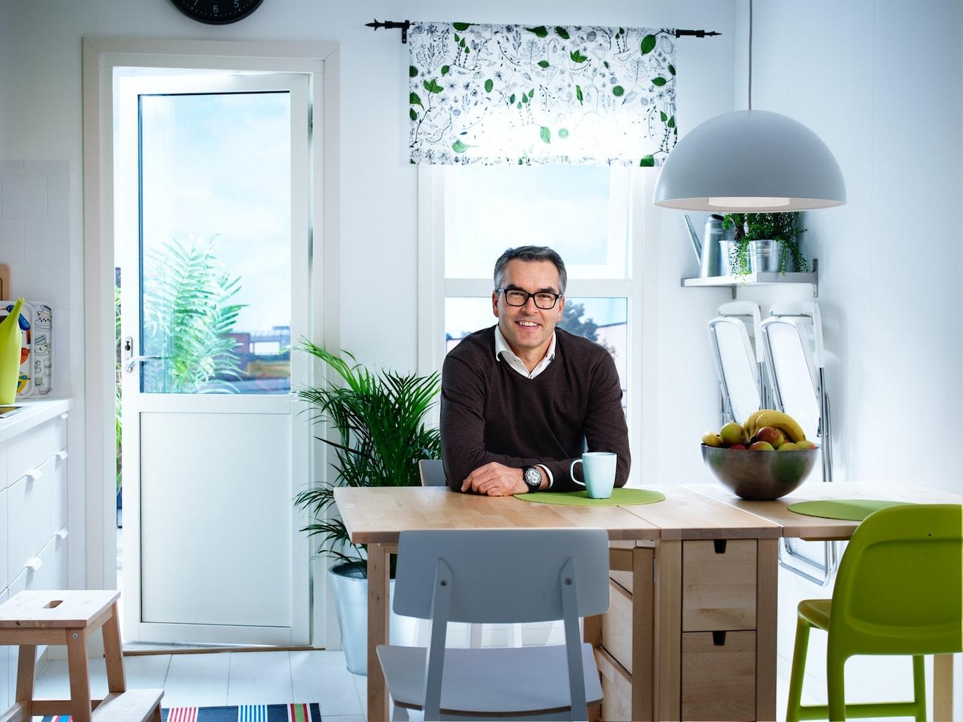 Mies istuu vaaleassa keittiössä kahvikupin äärellä.