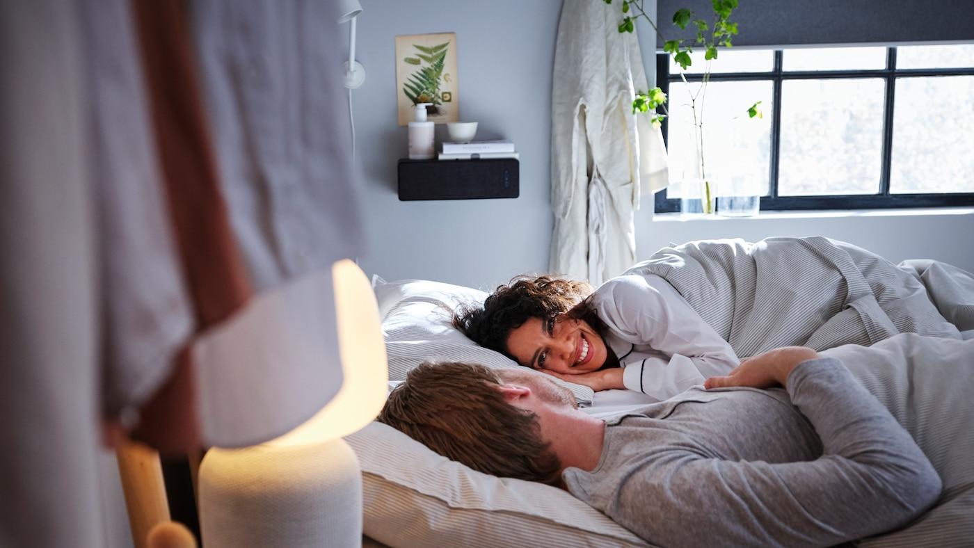 Mies ja nainen makaamassa sängyllä. Yöpöydällä on SYMFONISK- WiFi kaiutin lamppu ja taustalla älyverhot.