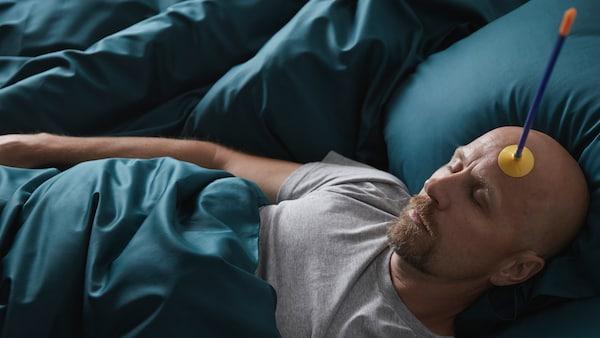 Mies nukkuu pehmeiden LUKTJASMIN-vuodevaatteiden keskellä, otsassaan lasten lelunuoli.