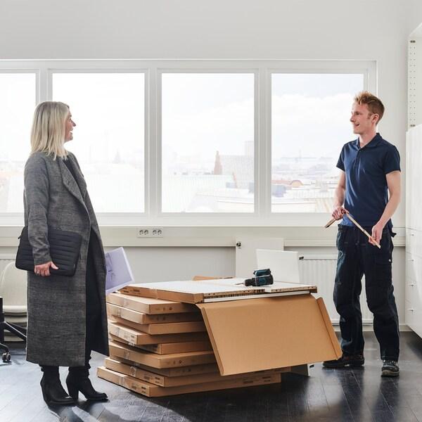 Mies purkamassa pakkauslaatikoita huoneessa. Nainen keskustelee hänen kanssaan.