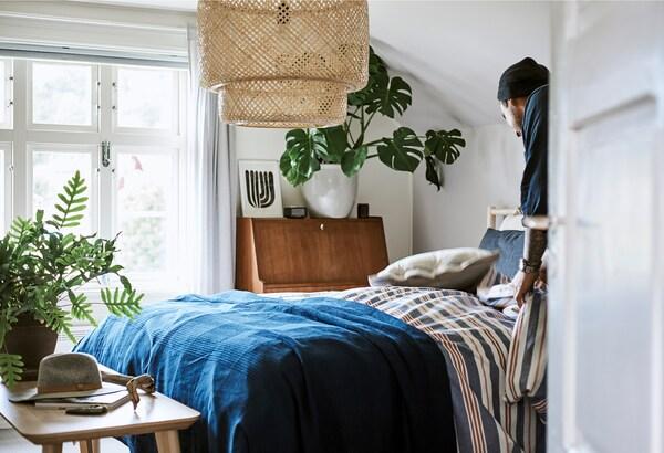 Mies sijaa vuodetta, jossa on raidallinen sini-puna-valkoinen päiväpeitto ja tummansininen huopa. Huoneessa on myös iso punottu SINNERLIG bambu kattovalaisin.