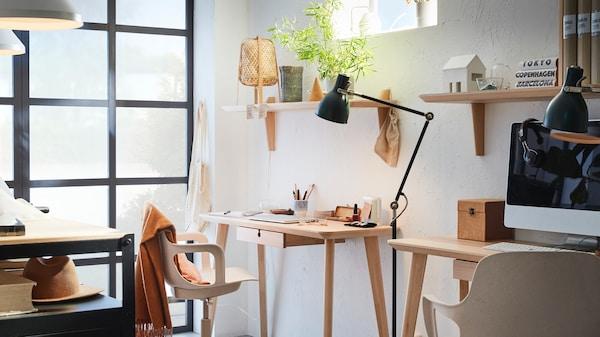 Miestnosť prispôsobená na prácu z domu. Stoly pripevnené k stene, stolové lampy, poličkami a kvetinou.