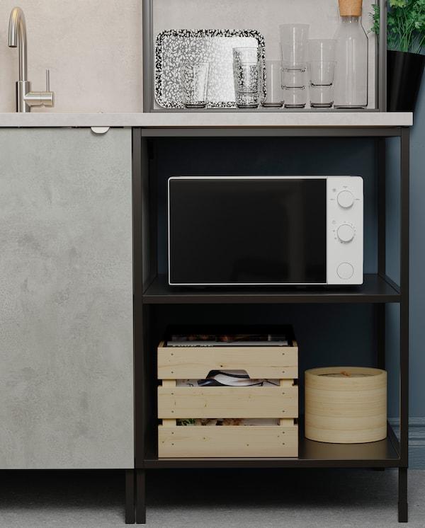 Mikrotalasna pećnica i dve drvene kutije postavljeni su na otvorene police ispod kuhinjske radne ploče. Pored se nalazi ormarić s vratima u imitaciji betona.