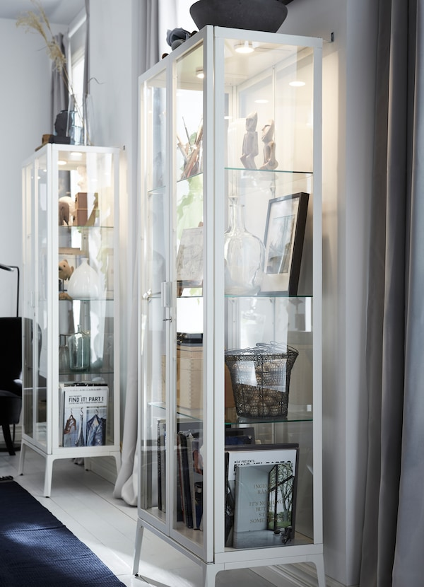 MILSBO خزانة زجاجية مؤطّرة بأبواب زجاجية لون أبيض مع مصابيح مدمجة بالداخل باستخدام إضاءة VAXMYRA LED.