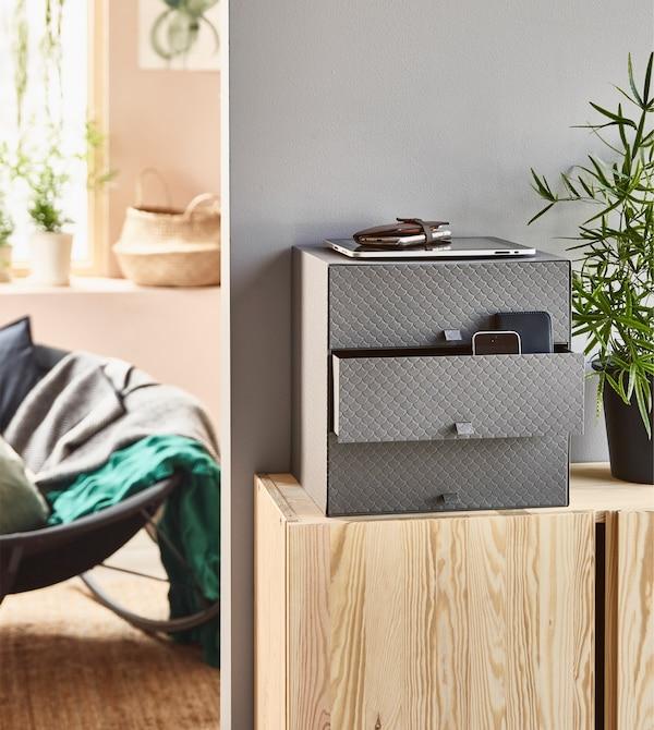 Mini cómoda PALLRA en gris oscuro sobre un armario de madera.