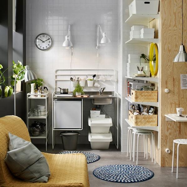 Mini-cuisine avec table à induction mobile et petit réfrigérateur. Une desserte et des tablettes murales complètent le rangement.