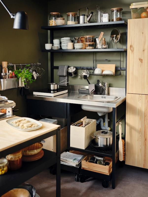 Mini-kuchnia RÅVAROR z wiszącą suszarką do naczyń i haczykami, wypełniona naczyniami i skrzynkami RÅVAROR.