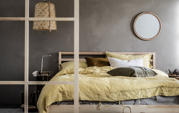 Minimalistička spavaća soba sivih zidova i neutralna paleta, drveni detalji, TARVA francuski ležaj, i KNIXHULT lampa.