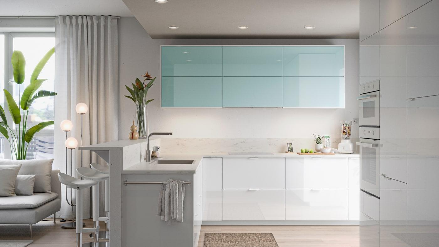 Minimalistisk kjøkken med høyglansede dører i hvitt og turkis, frukt på ei skjærefjøl og i en blender.