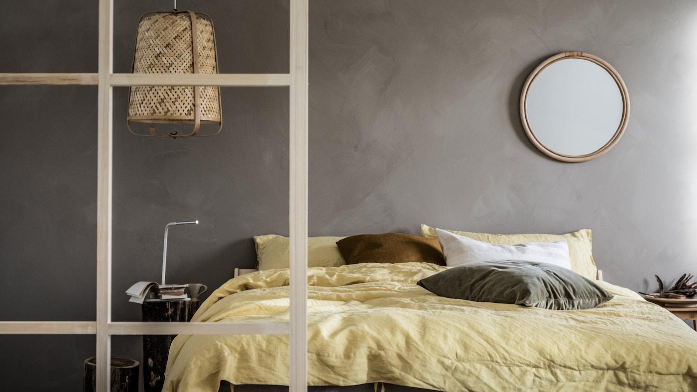Minimalistisk soveværelse med grå vægge og et afdæmpet farvetema, detaljer af træ, en NEIDEN dobbeltseng og en KNIXHULT lampe.