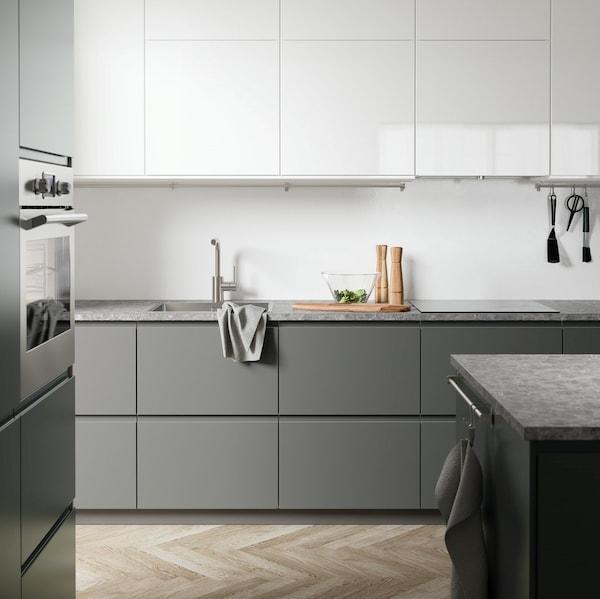 Minimalistyczna kuchnia z szarymi i białymi frontami VOXTORP.