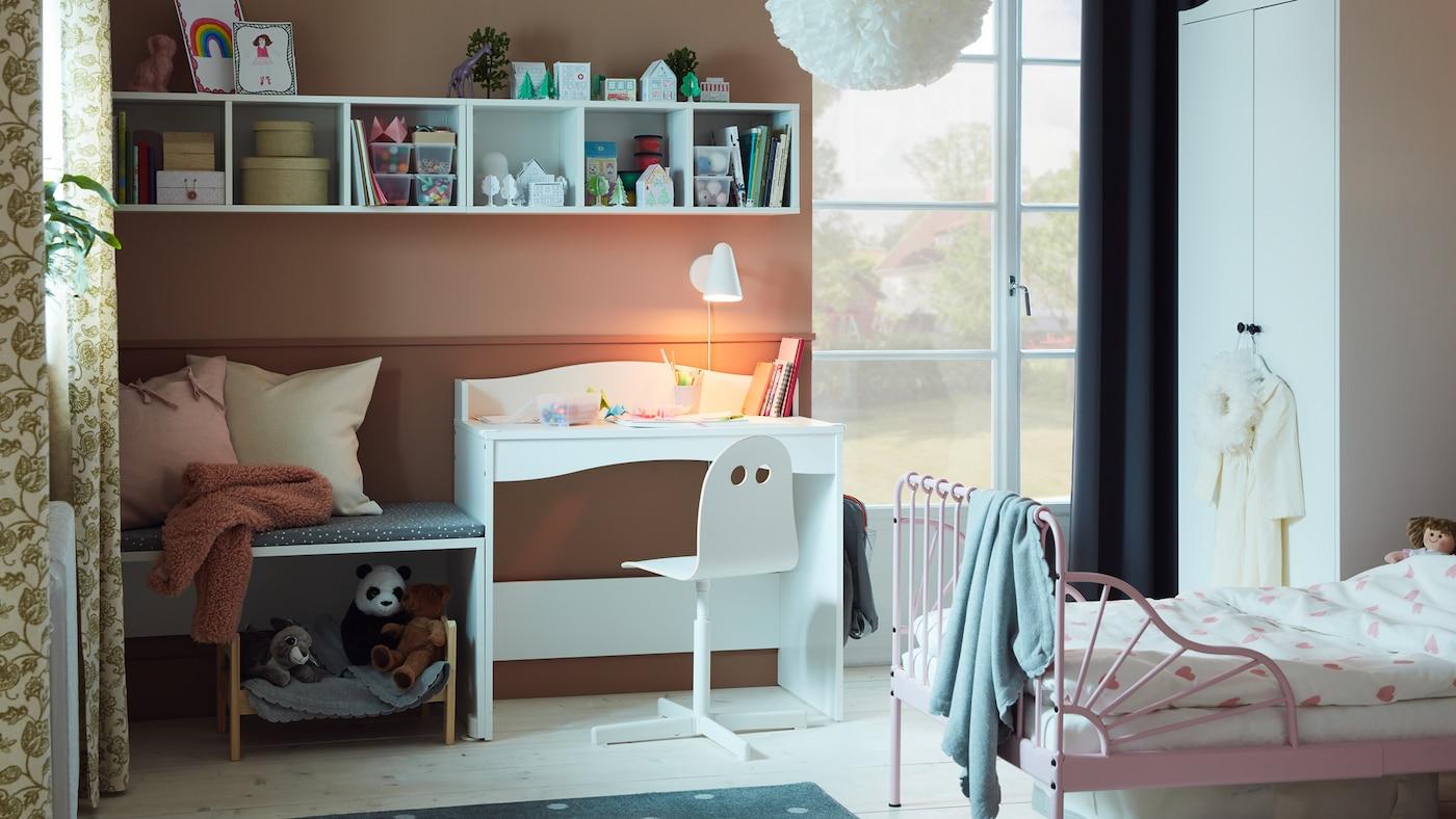 라이트핑크 색상의 MINNEN 민넨 길이조절침대+침대갈빗살, 화이트 책상, 책, 인형이 있는 아이 침실.