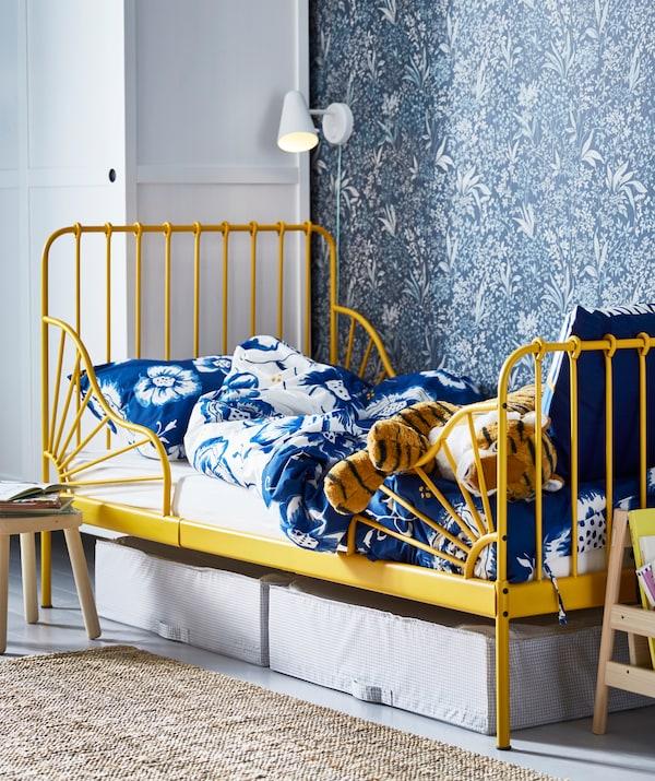 MINNEN Bettgestell ausziehbar, gelb mit Blütenbettwäsche. Unter dem Bett sind Kästen zu sehen, darüber eine Leuchte.