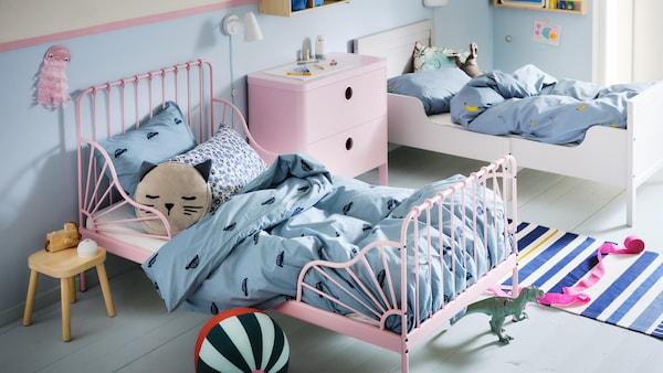라이트핑크 MINNEN 민넨 길이조절침대와 블루 VÄNKRETS 벵크렛스와 BARNDRÖM 바른드룀 침구로 꾸민 화이트 침대가 놓인 어린이 침실.