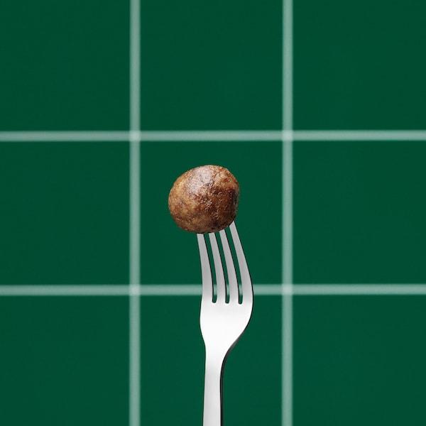 調理済みのイケアのプラントボール1個が、上向きのシルバーのフォークの先端に刺さっている。背景はグリーンとホワイトのチェック模様。