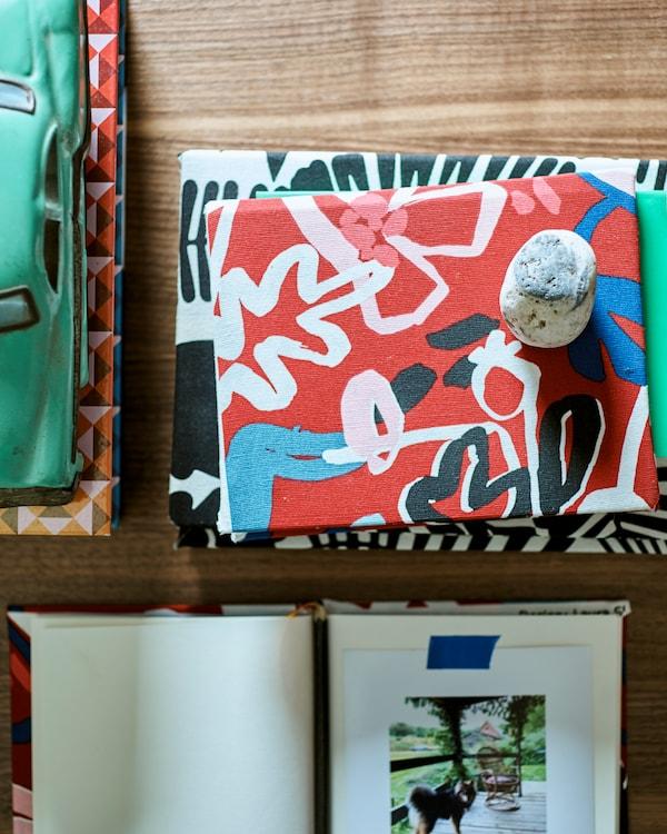 Mintás textíliába csomagolt könyvek egy fa asztalon, zöld játékautóval.