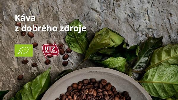 Miska s kávovými zrnky, kolem jsou položené kávové listy, na obrázku logo certifikace