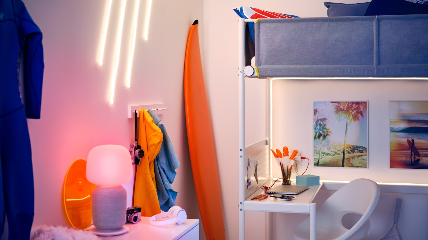 Místnost s rámem vysoké postele VITVAL, surfovací prkno, světelné pásky LED MYRVARV na stěně a stolní lampa s reproduktorem WiFi..
