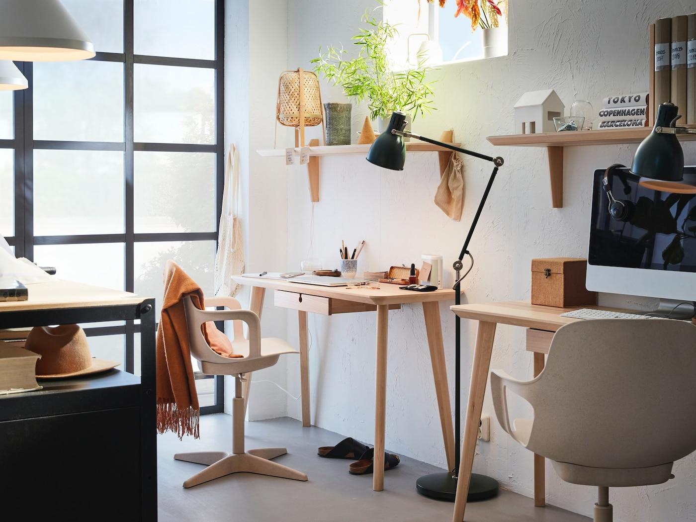 Místnost uzpůsobená pro práci z domu. Stoly připevněné ke zdi, se stolními lampami, poličkami a květinou.