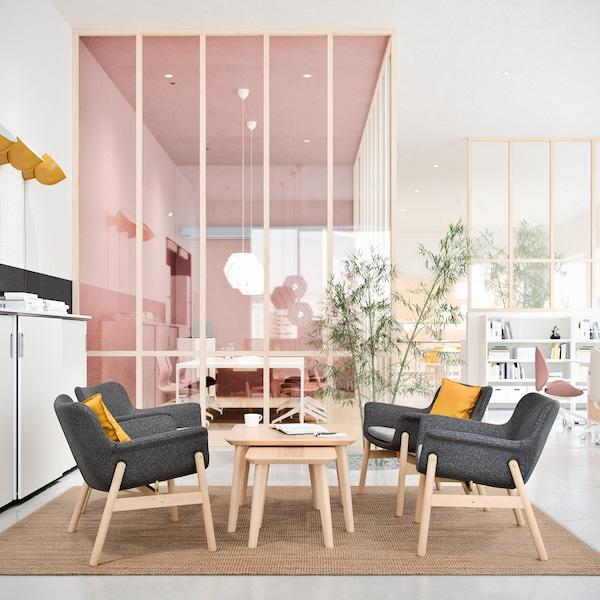 Místo k odpočinku se čtyřmi křesly oddělené růžovou stěnou od zbytku kanceláře.