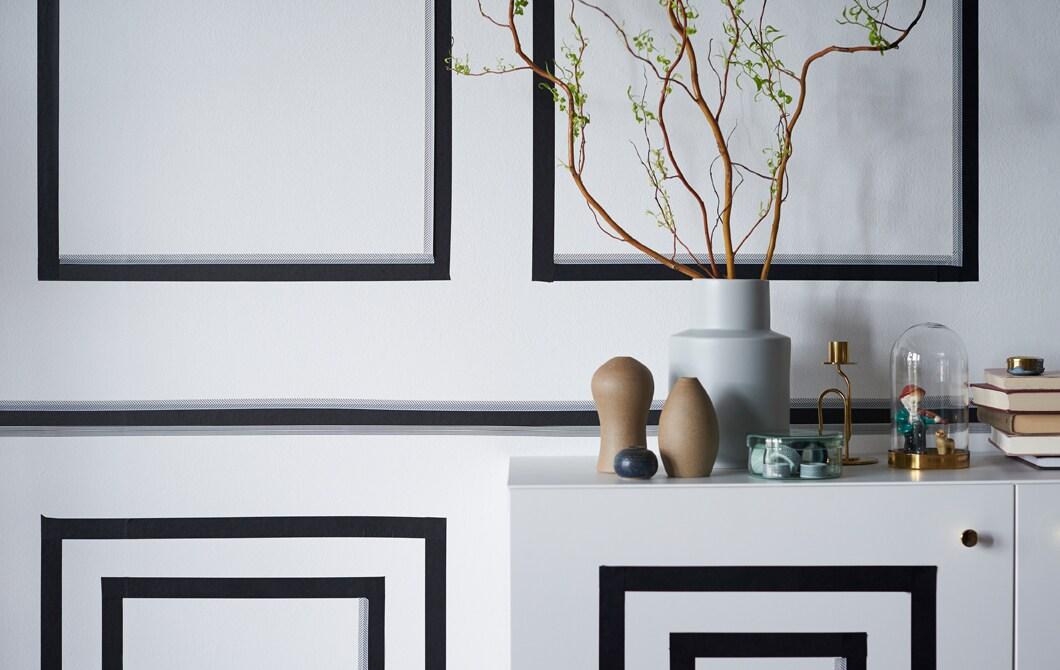 Mit schwarzem Klebeband in quatratischen Formen dekorierte weiße Wand & Kommode