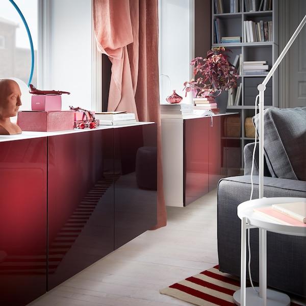 مجموعة خزانة BESTÅ بيضاء تتضمن أبواب فائقة اللمعان بلون أحمر داكن ـ بني داكن مثبتة بالحائط أسفل نافذة.