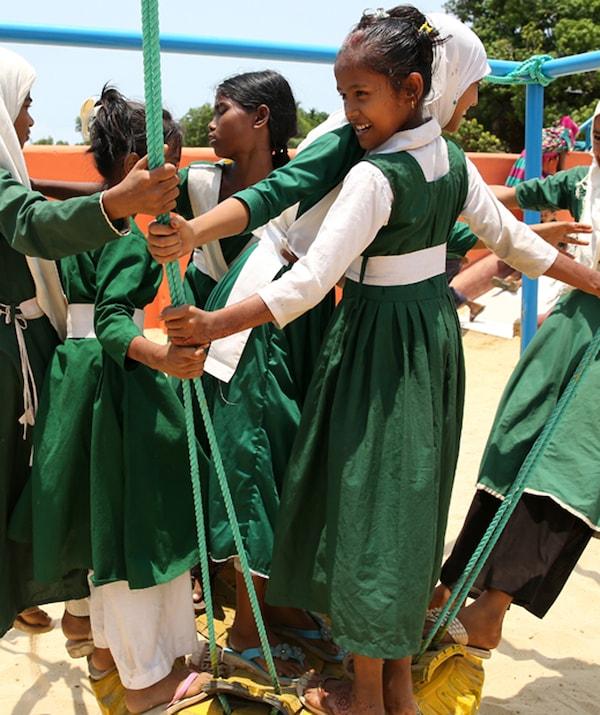 مجموعة من البنات يرتدين فساتين خضراء يلعبن على أرجوحة حبل في مكان خارجي.