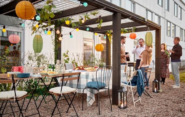 مجموعة من الناس يقفون بجوار صف كراسي وطاولات صغيرة مجهزة لحفل في ظل برجولا مزينة في فناء.