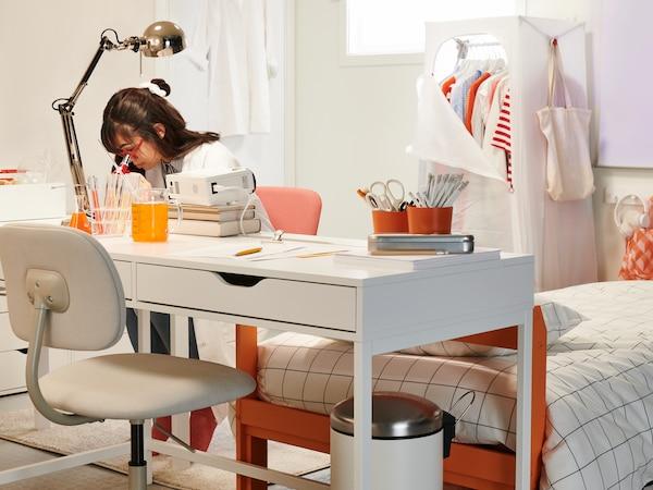 مكتب أبيض مع كرسي دوار في أحد الجوانب،وطالب يجلس على الجانب الآخر، في غرفة طلابية غريبة الشكل.