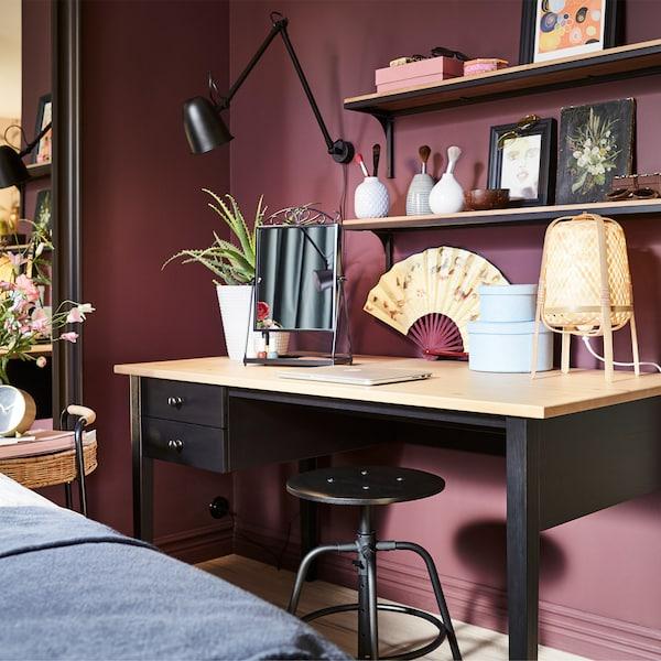 مكتب من خشب الصنوبر الأسود والصلب، ومصباح حائط أسود، ومصباح طاولة مصنوع من خشب الخيزران ومقعد أسود.