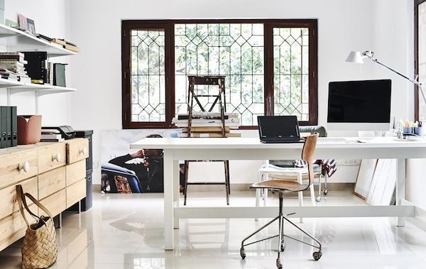 مكتب منزلي أبيض مع صندوق أدراج خشبي ورفوف.