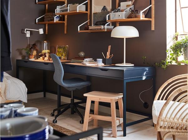 مكتب منزلي مع مكتب أزرق داكن، ومجموعة رفوف مثبتة على الحائط من الخيزران، ومصباح طاولة أبيض ومقعد من خشب البتولا.