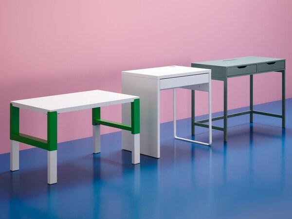 مكتب PÅHL أبيض/أخضر ومكتب MICKE أبيض ومكتب ALEX رمادي فيروزي في مجموعة مع جدار وردي وأرضية زرقاء.
