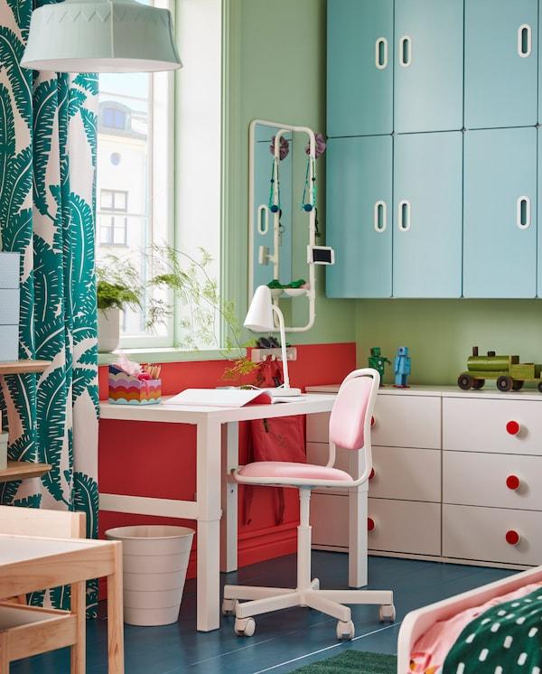 مكتبPÅHL، وكرسي مكتب أطفال وردي/أبيض، وحاوية مهملات بيضاء ومصباح طاولة أبيض بجوار نافذة.