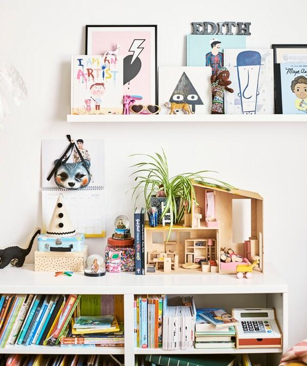 مكتبة أطفال مملوءة بكتب وألعاب، ومن أعلى بيت دمية وعلب ألعاب، مع رف كتب على الحائط.