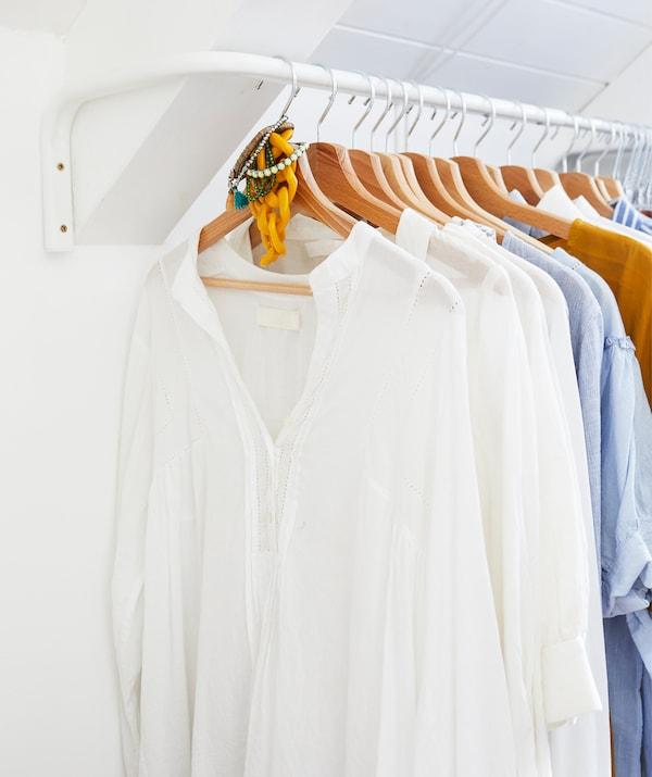 ملابس معلقة على علاقات خشبية على سكة تعليق بيضاء في غرفة بيضاء.